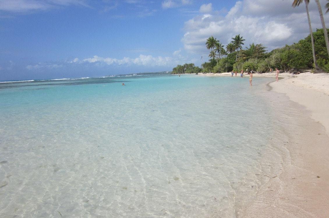 Plage de sable blanc et d'eau turquoise dans les Caraïbes